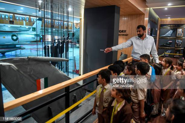 Students look at a part of an Indian Mig21 fighter aircraft which was being flown by Indian pilot Wing Commander Abhinandan Varthaman whose plane was...