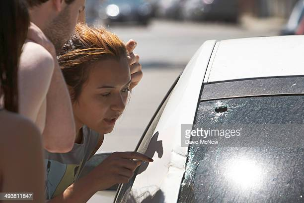 Students look at impact damage aroudn a bullet hole on a car at a crime scene May 25 2014 in Isla Vista California According to reports 22 year old...