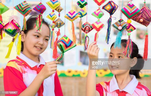 Students look at multicolored sachets at a primary school to welcome the upcoming Dragon Boat Festival or Duanwu Festival on June 4 2019 in Hohhot...
