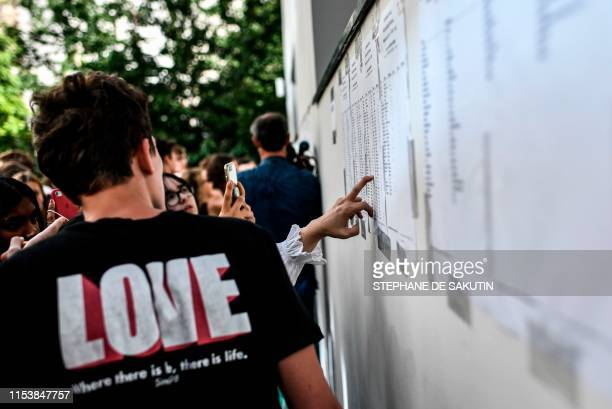 Students look for their names as they check the results of the baccalaureat exam at the Fresnel high school in Paris, on July 5, 2019. - French high...