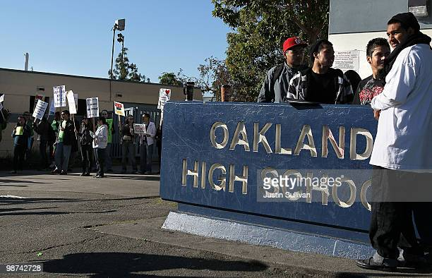 Students look on as teachers hold signs while they protest during a oneday strike outside of Oakland High School April 29 2010 in Oakland California...