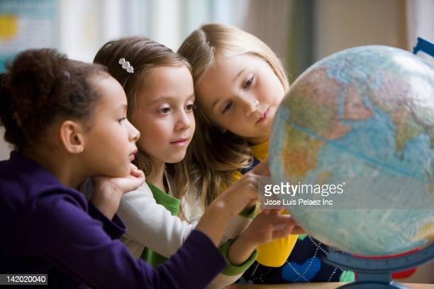 Students looking at globe in classroom