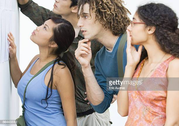 students looking at results posted on wall, side view - baccalaureat stock pictures, royalty-free photos & images