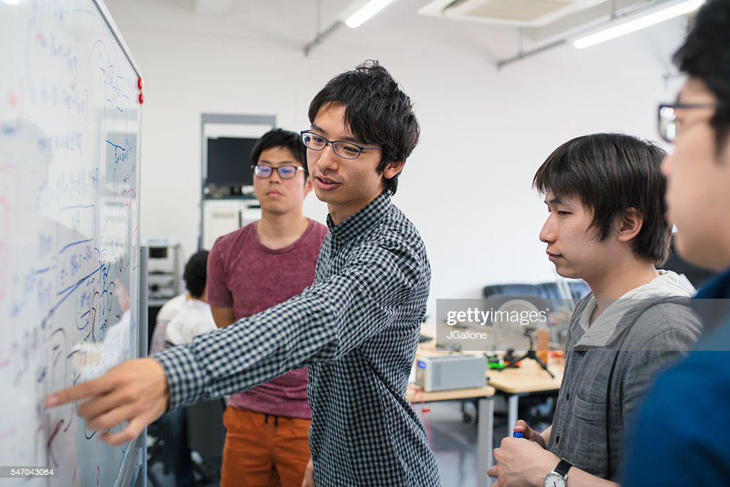 Students looking at scientific formula : Stock Photo