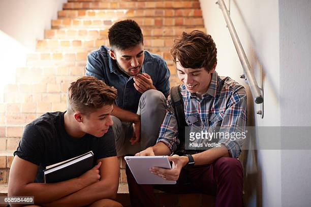 Students looking at tablet, sitting on staircase