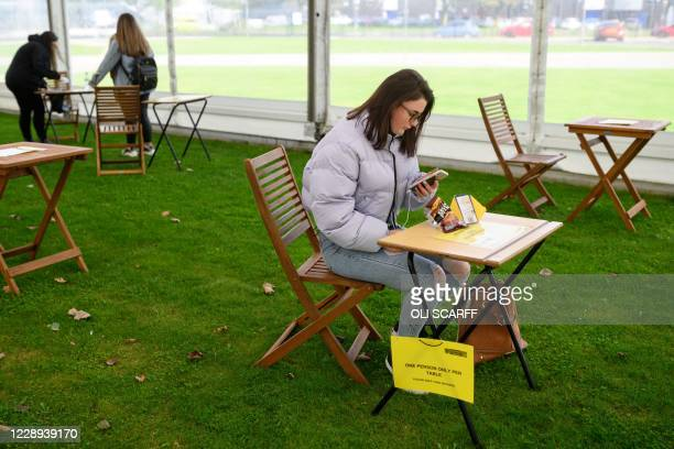 Students maintain social distancing in a large marquee erected by the university to create an additional socially distanced rest area to help...