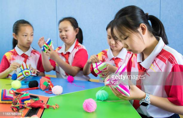 Students make multicolored sachets at a primary school to welcome the upcoming Dragon Boat Festival, or Duanwu Festival, on June 4, 2019 in Hohhot,...