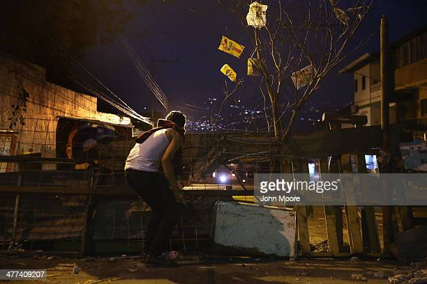 Students man a barricade in downtown while watching for Venezuelan security forces before dawn on March 9 2014 in San Cristobal the capital of...