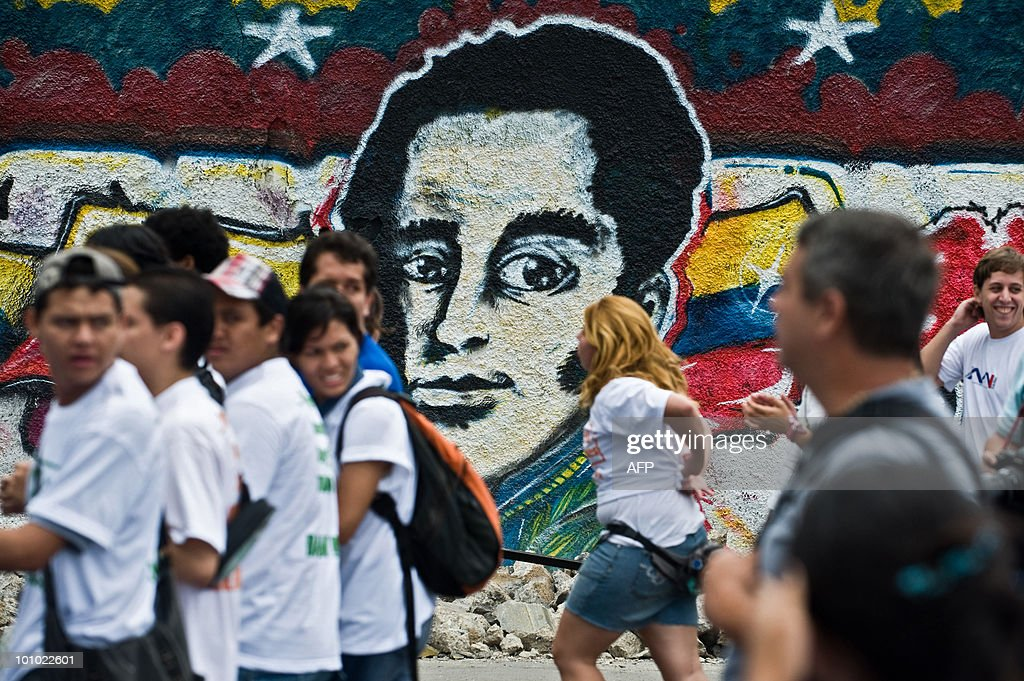 Students march in front of a grafitti depicting Venezuelan hero Simon Bolivar during a protest of students and teachers in demand of a higher budget for educaction in Caracas on May 27, 2010. AFP PHOTO / Miguel GUTIERREZ