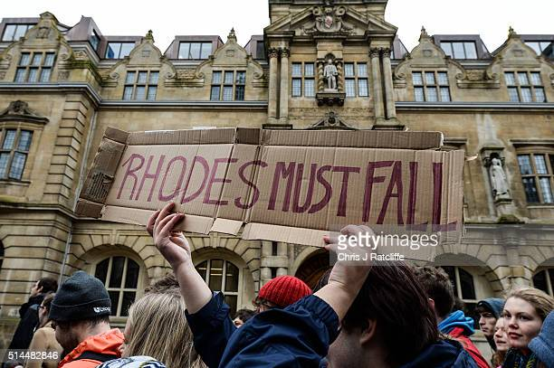 Students march past Oxford University's Oriel College and the statue of Cecil Rhodes that they are campaigning to be removed from the building on...