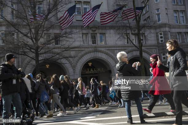 Students march past the Trump International Hotel during the ENOUGH National School Walkout rally in Washington DC US on Wednesday March 14 2018...