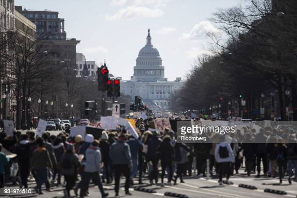 Students march towards the US Capitol building during the ENOUGH National School Walkout rally in Washington DC US on Wednesday March 14 2018...
