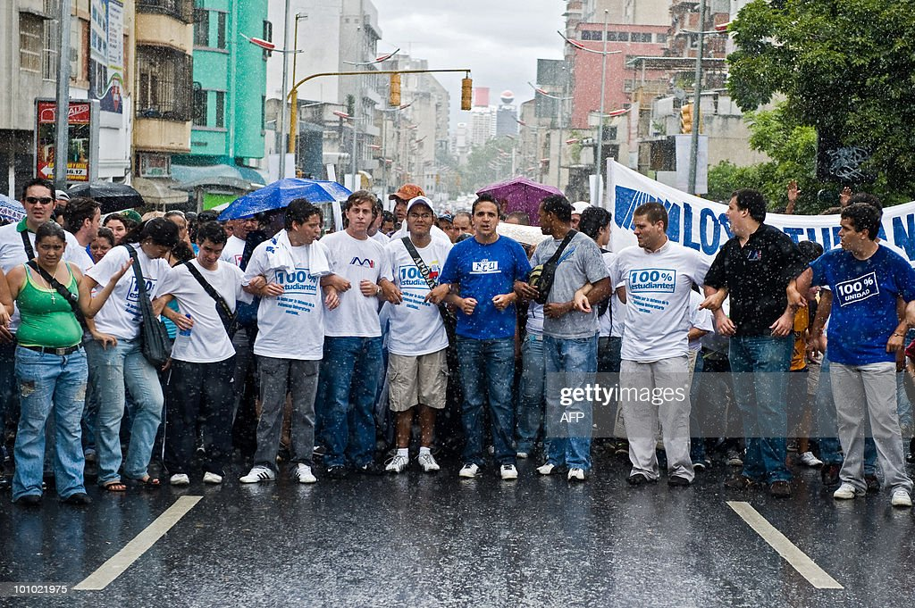 Students march under the rain during a protest of students and teachers in demand of a higher budget for educaction in Caracas on May 27, 2010. AFP PHOTO / Miguel GUTIERREZ