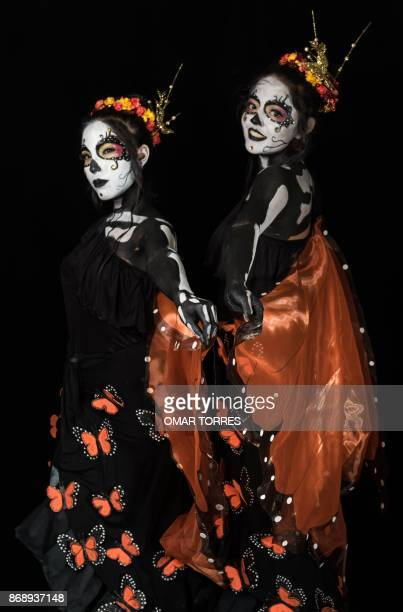 Students Noemi Robles and Martha Rodriguez Fernandez pose for a photograph disguised as Catrinas during a Catrinas competition at the University of...