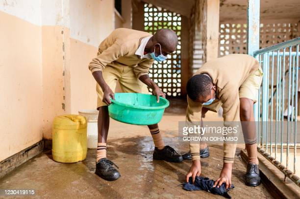 Students of Ayany Primary School clean the floor before the class in morning of the official re-opening day of public schools on January 4 in Kibera...