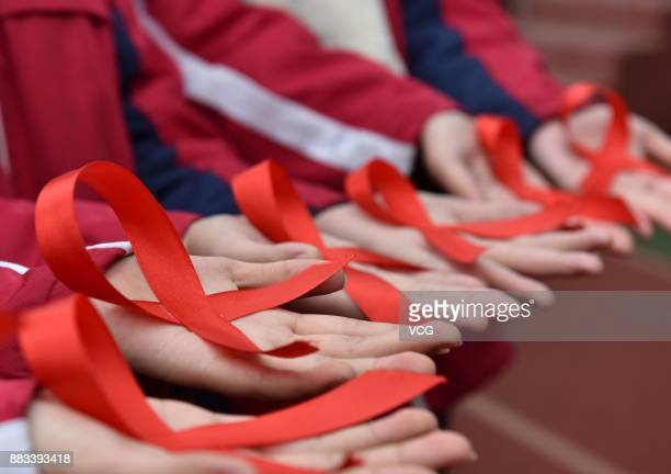 Students of Chaohu No2 Middle School show handmade red ribbons on November 30 2017 in Chaohu Anhui Province of China Chaohu No2 Middle School...
