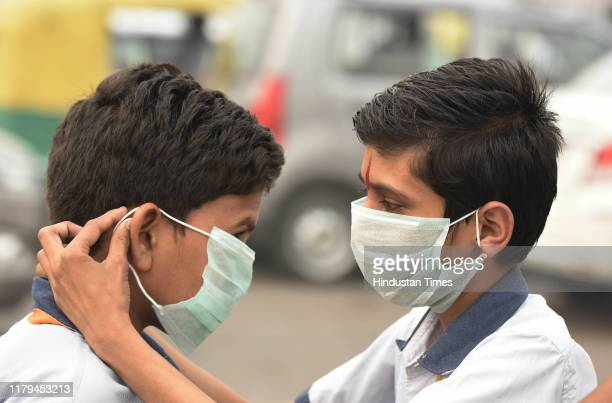 Students of Gyan Jyoti School from Chittorgarh in Rajasthan help each other to put on pollution masks while on an educational tour at Vijay Chowk on...