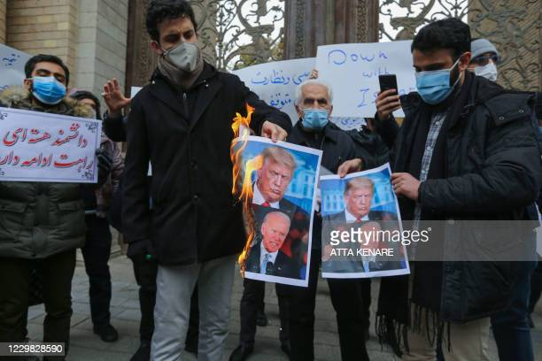Students of Iran's Basij paramilitary force burn posters depicting US President Donald Trump and President-elect Joe Biden, during a rally in front...