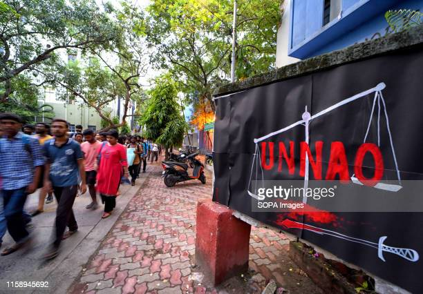 Students of Jadavpur University walk past a black poster during the Protest against the Rape Case of Unnao. A 17 year old girl was gang raped on June...