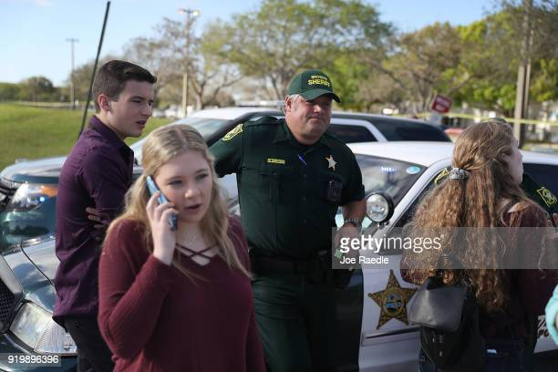 Students of Marjory Stoneman Douglas High School speak with Broward County Sheriff officers Brad Griesinger as he guards the front gate of the school...