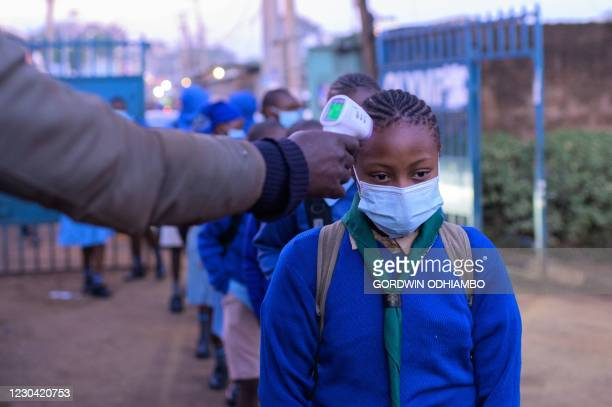 Students of Olympic Primary School wait in a line to have their temperatures measured at the entrance of the school in the early morning of the...