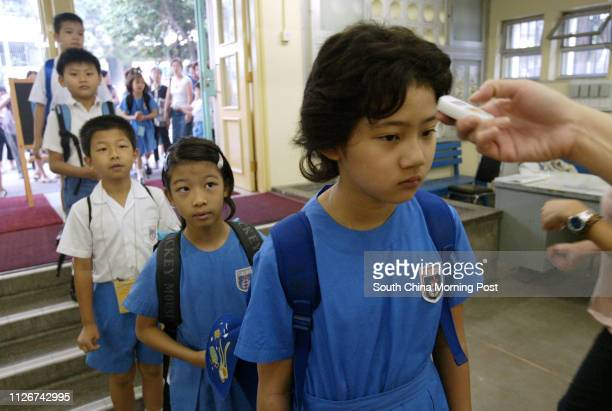 Students of SKH Yat San Primary School line up to have temperature check for the SARS precaution on the first day of the new school year. 01...