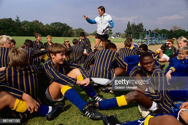 Students of St David's Marist College a Roman Catholic school in Johannesburg South Africa sit and chat during soccer practice