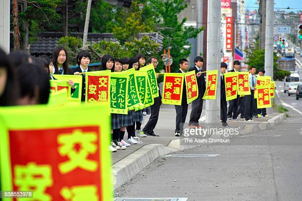 Students of Sunagawa High School line up with holding banners 'No Drink Driving' on a road raise awareness on the first anniversary of the car...