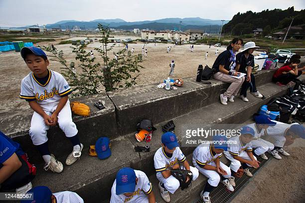 Students of Takada Elementary school attend a baseball game next to a devasted area prior to the sixth month anniversary of the March 11 earthquake...