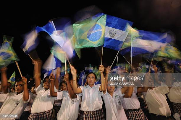Students of the Santa Cristina middle school of San Luis Talpa wave the national flags of El Salvador and Brazil upon the arrival of Brazilian...