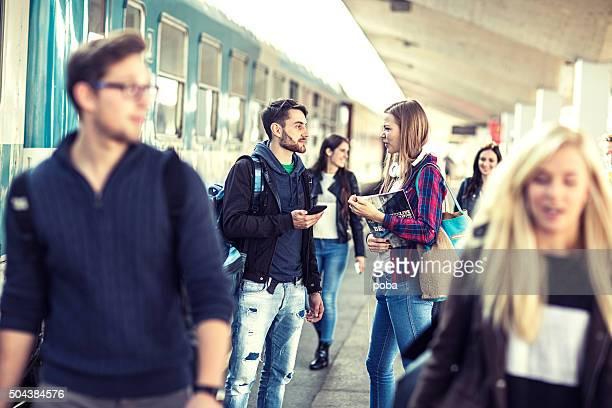 students  on a  train station  platform