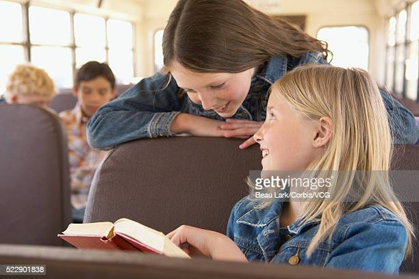Students on school bus looking at book