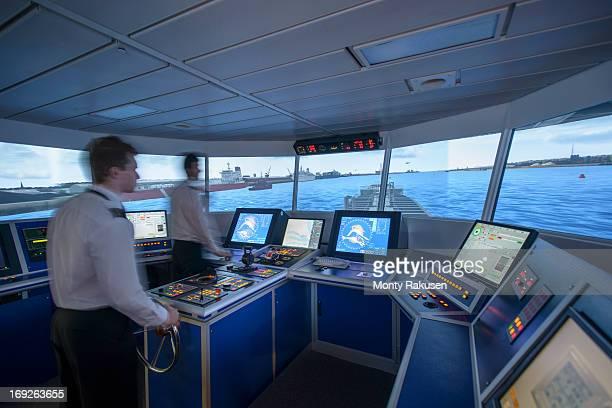 Students operating equipment in ship's bridge simulation room
