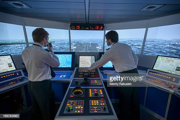 students operating equipment in ship's bridge simulation room - slave ship stock photos and pictures