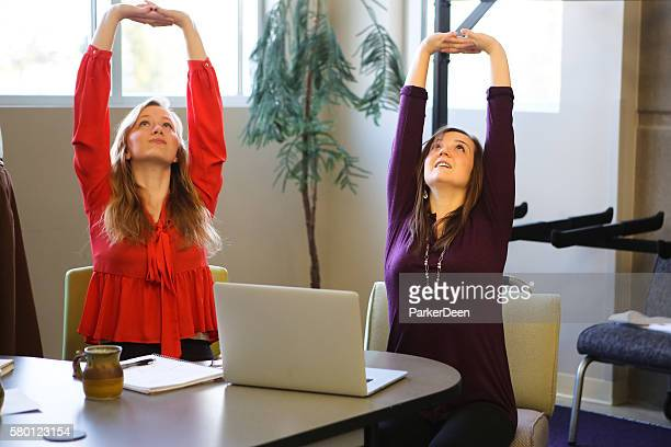 students or young business women doing yoga stretching working studying - pauze nemen stockfoto's en -beelden