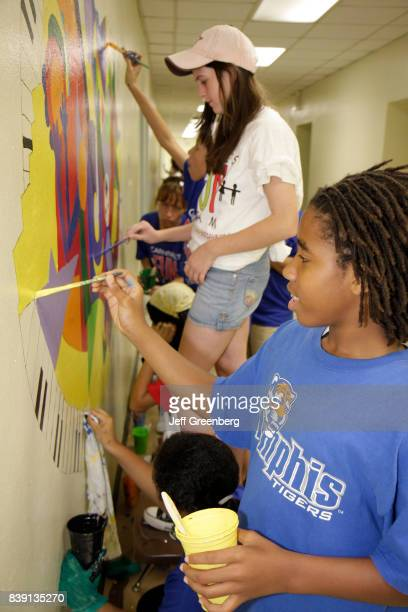 Students painting a mural in the hallway in Citrus Grove Middle School at Hands on Miami Day