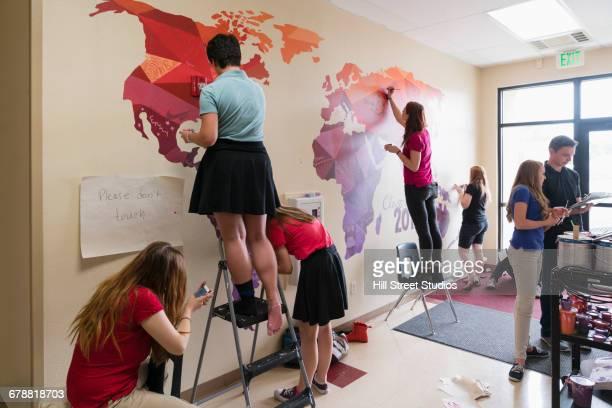 students painting mural of map on school wall - pintar mural fotografías e imágenes de stock