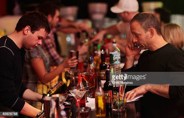 Students pair up to watch each other prepare drinks at the New York Bartending School December 5 2008 in New York City Enrollment is up at the...