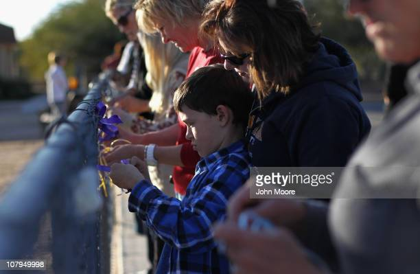 Students parents and teachers attach ribbons to a fence at Mesa Verde Elementary School to honor slain student Christina Green 9yearsold on January 9...