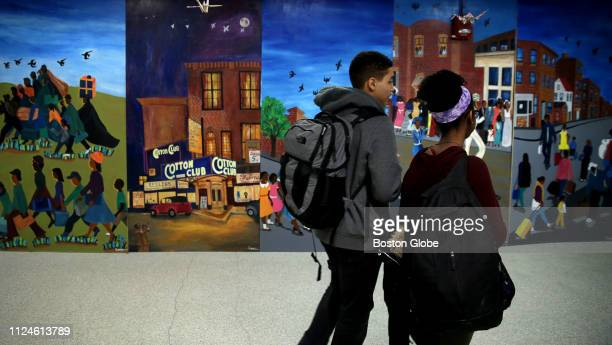 Students pass by a mural that is part of a student art exhibit highlighting the Harlem Renaissance at the John D. O'Bryant School of Mathematics and...