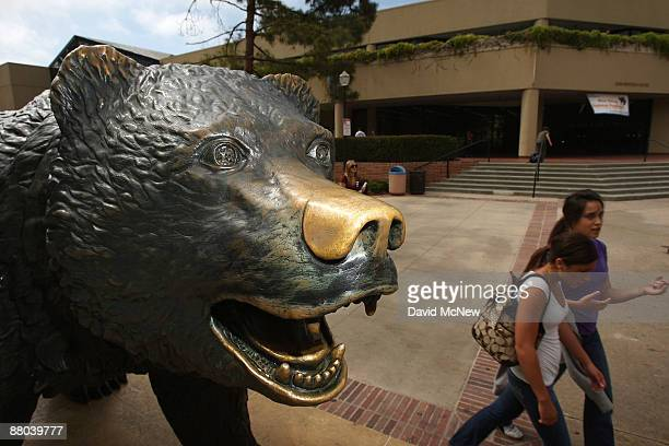 Students pass the bronze statue of their campus mascot The Bruin a California grizzly bear at University of California Los Angeles as the prospect of...