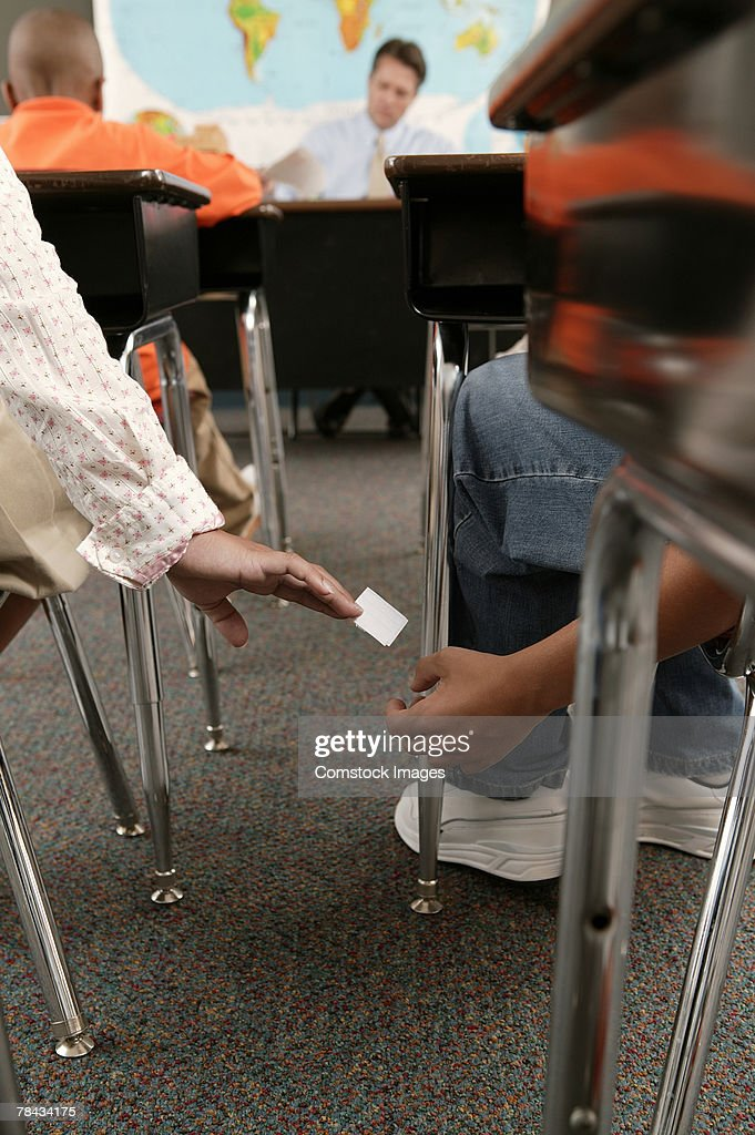 Students passing note in class : Stockfoto