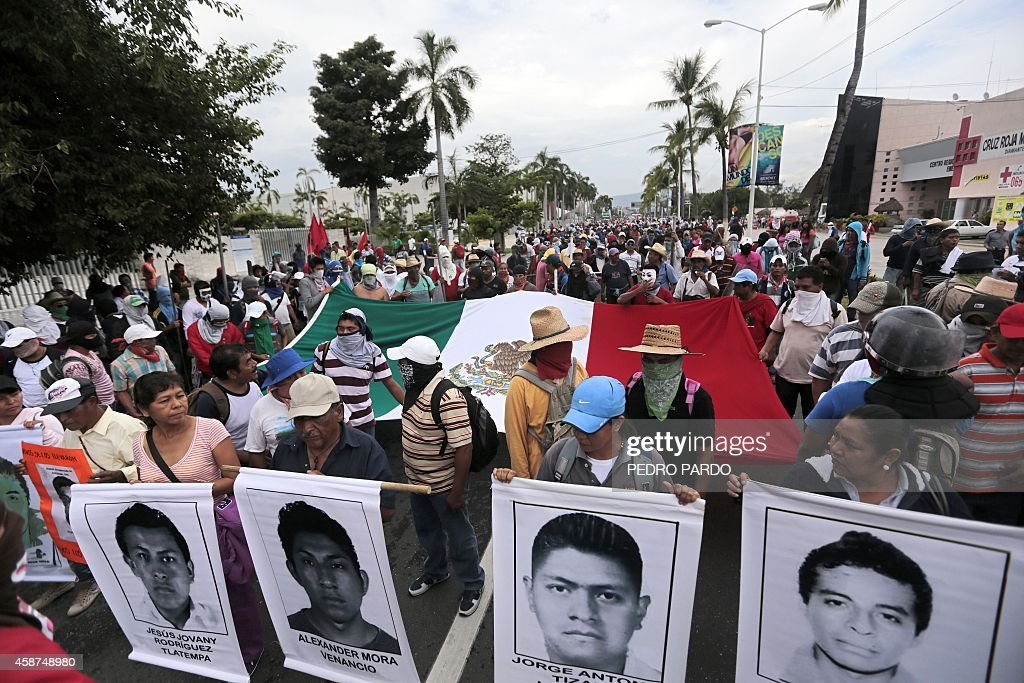 Students, peasants and other people demonstrate against the suspected massacre of 43 missing Mexican students, in the proximities of Acapulco's airport, in the Mexican state of Guerrero State, on November 10, 2014. Protesters angry at the suspected massacre threw stones and a firebomb at riot police in the Pacific resort of Acapulco on Monday, injuring 11 officers. Around 300 students, some wearing masks and armed with sticks and machetes, were joined by some parents of the 43 missing young men as they marched toward the city's airport, but police blocked their way. Mexico was confronted with one of the grisliest massacres in years of drug violence after gang suspects confessed to slaughtering 43 missing students and dumping their charcoaled remains in a river.