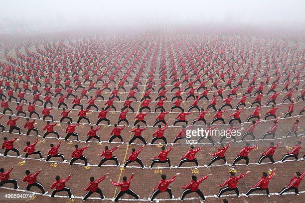 Students perform callisthenics in the fog during the opening ceremony of the Teenagers in Henan Shaolin Soccer Training Base in Dengfeng, November...