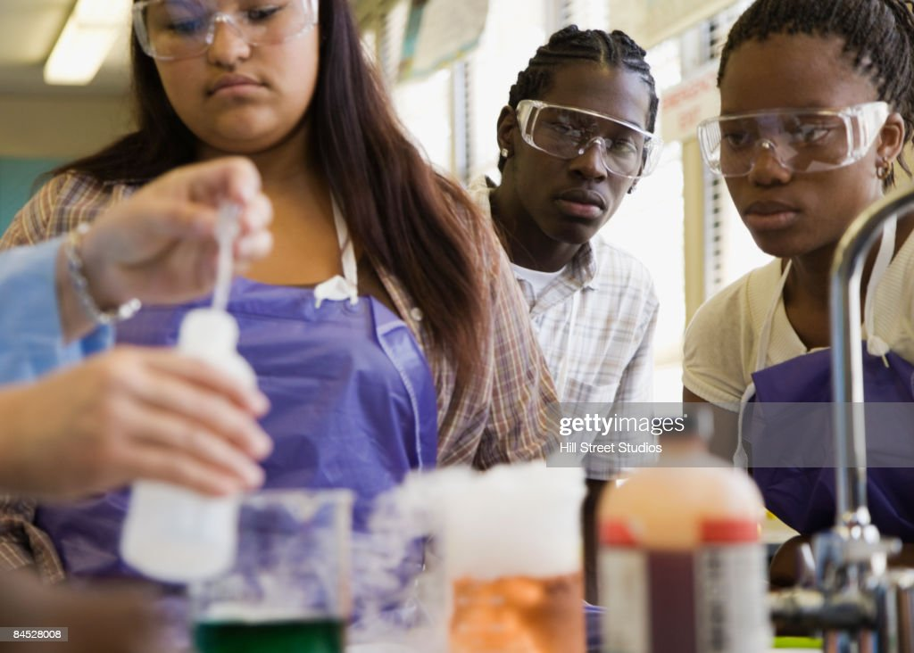 Students performing experiment in chemistry lab : Stock Photo
