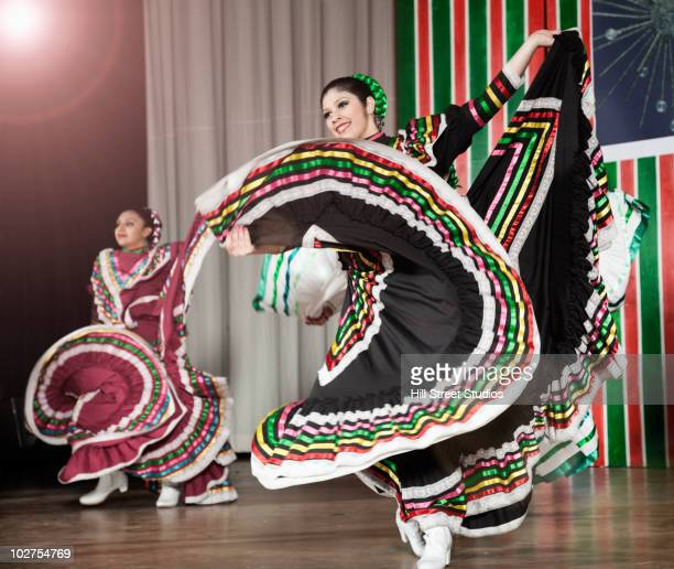 Students performing Mexican folk dance on stage