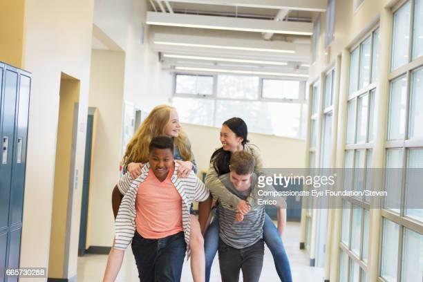 Students piggybacking in school hallway