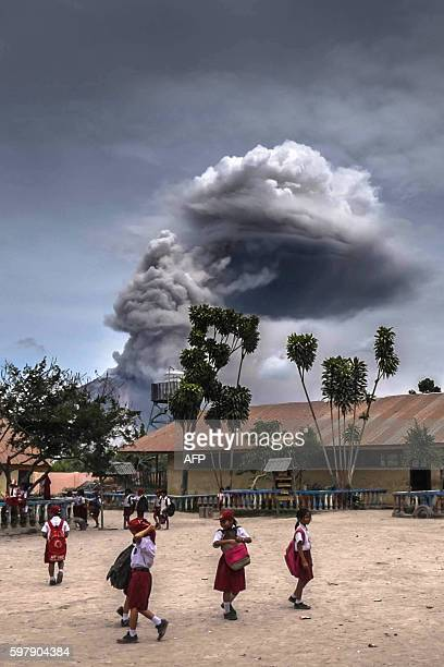 TOPSHOT Students play as mount Sinabung volcano spews thick volcanic ash in Karo North Sumatra province on August 30 2016 Many residents in the area...