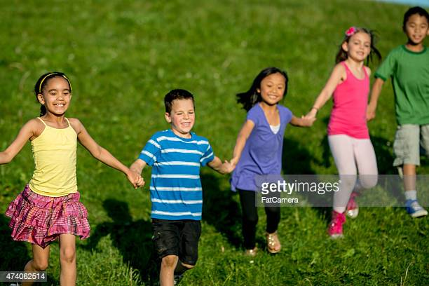 students playing a game at recess - kids playing tag stock photos and pictures