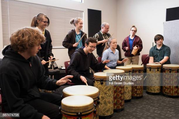 students playing bongo drums in high school band class - reggae stock photos and pictures